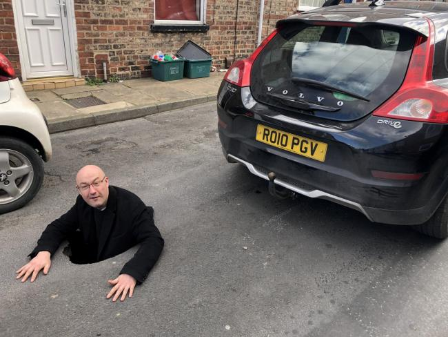 Grant Parker was driving his Volvo C30 in Granville Terrace, off Hull Road, York , when part of the road surface collapsed - opening up a hole in the road big enough for him to climb into. Photo: SWNS