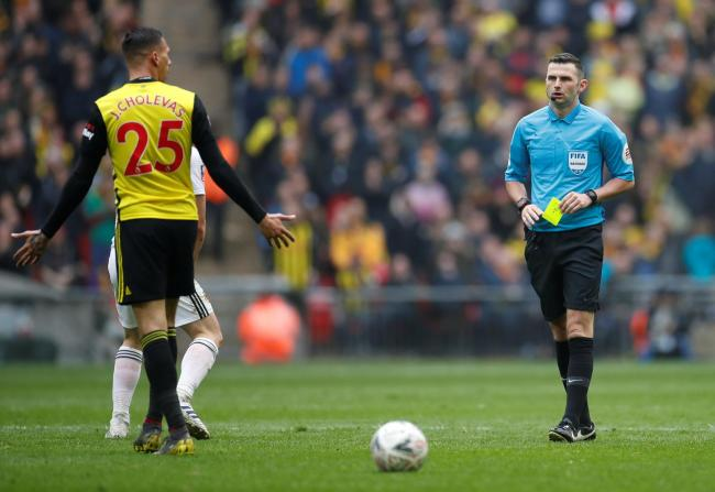 Michael Oliver awards a yellow card to Jose Holebas. Picture: Action Images