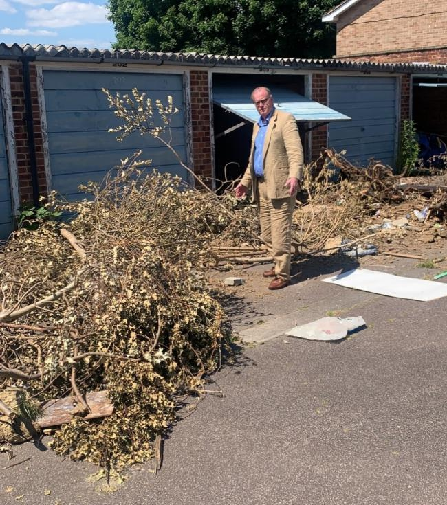 Cllr Nigel Bell points out that these trees have been left at the garages for nearly two weeks