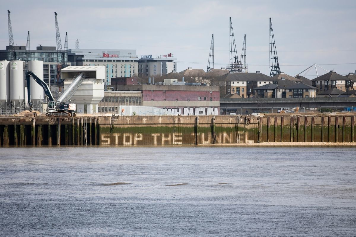 Activists jet-washed the slogan stop the tunnel onto the Thames embankment near the tunnels proposed location