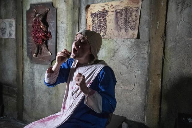 Harrow Times: Doctors Assistant applies the finishing touches to her makeup at the London Dungeon.  Credit: PA