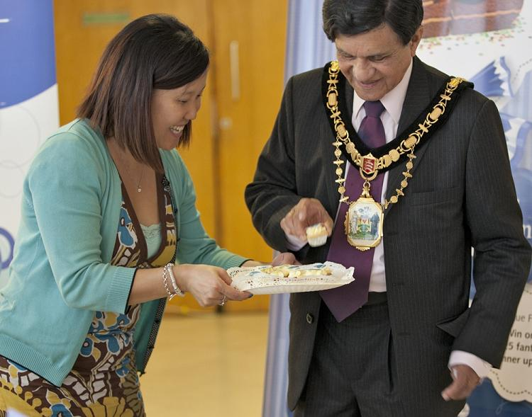 Mayor of Harrow, Councillor Nizam Ismail, helps himself to one of the cupcakes on Saturday (Photo: Husain Akhtar).