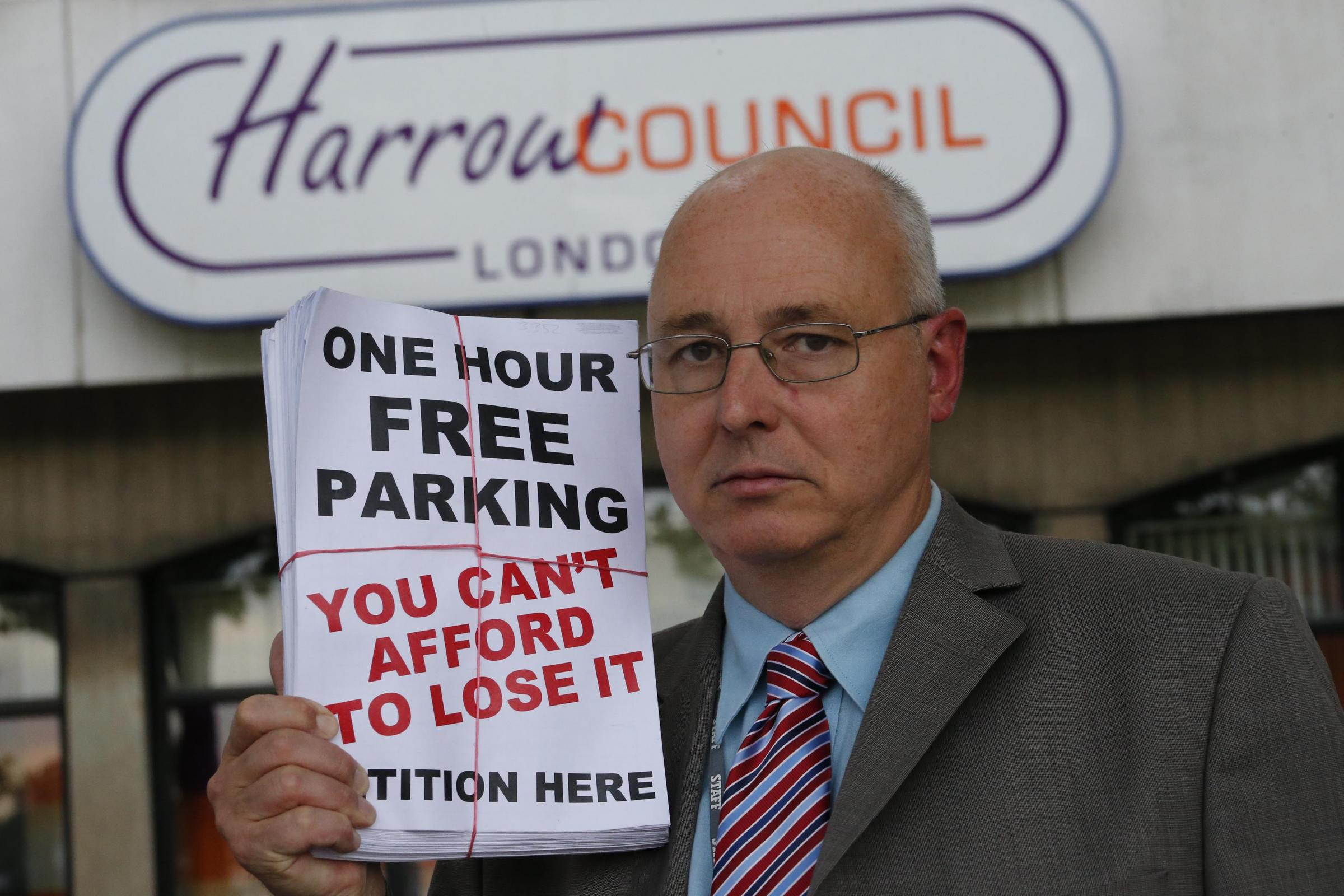 Councillor James Bond handing in his petition for North Harrow's hour free parking which was scrapped last year