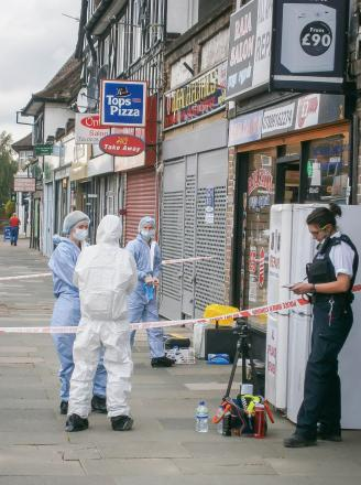 Police forensic teams at the scene of the attack yesterday