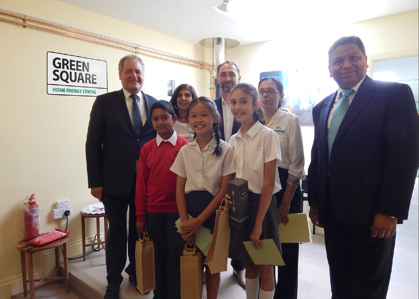 Bob Blackman MP (standing far left) and Cllr Ajay Maru (standing far right) join pupils from Grimsdyke School, Pinner, at a Green Square showroom opening in Hatch End